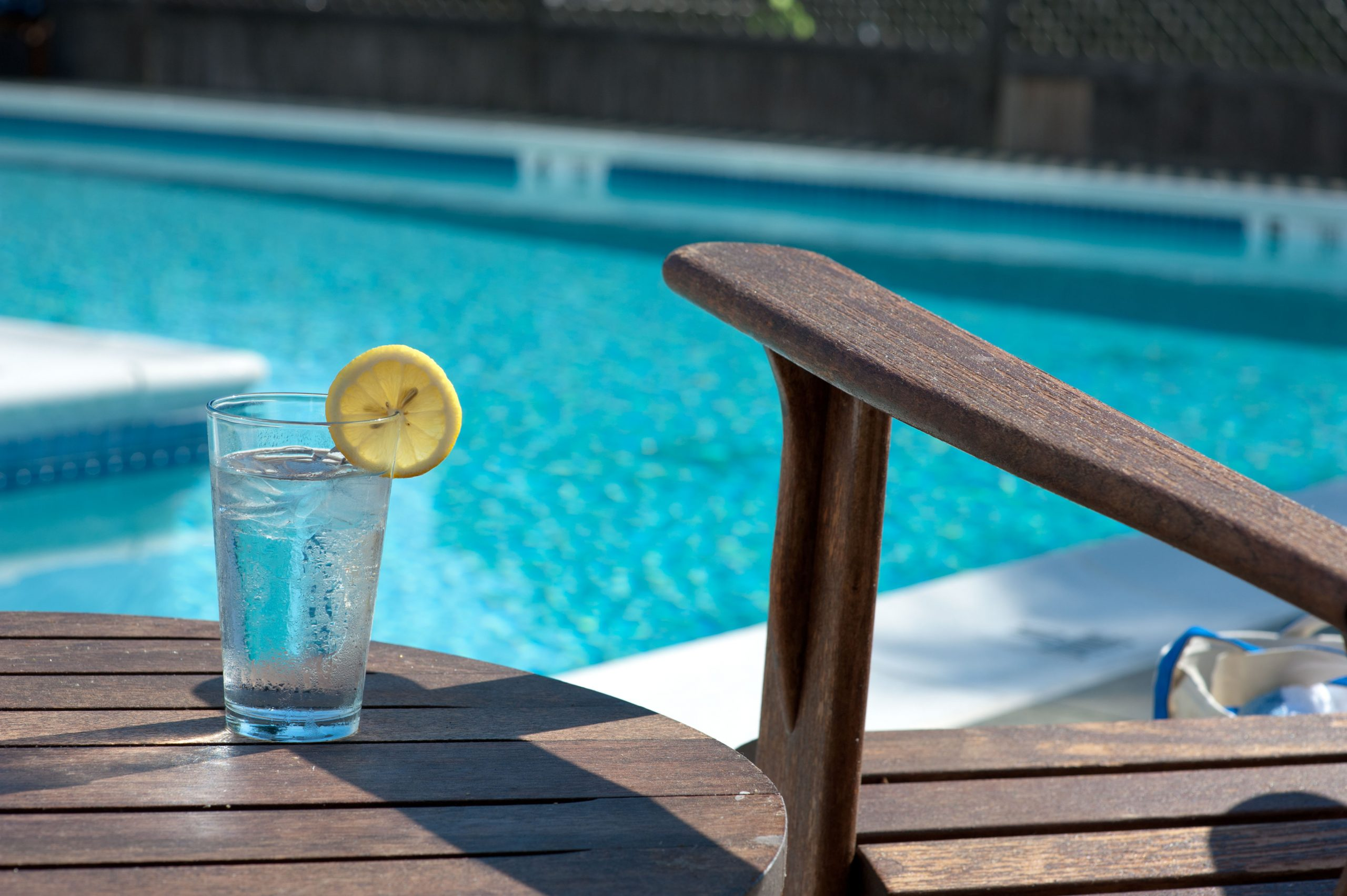 Glass of iced water with a lemon wedge facing the pool